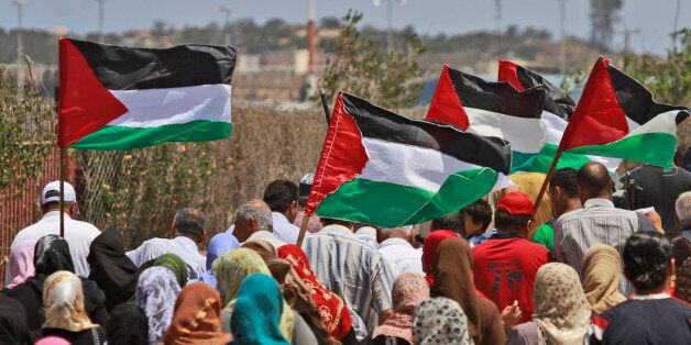 Palestinians, some holding national flags, approach the border line with Israel, seen in the background,...