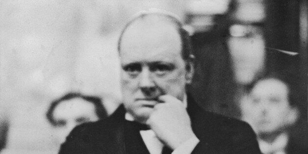 British statesman Winston Churchill (1874 - 1965) experiences a nail-biting moment during a meeting of...