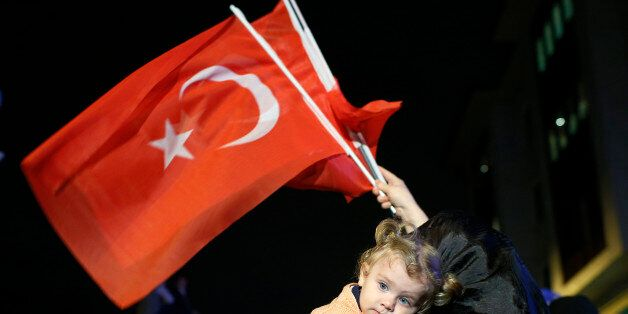 A supporters of Turkey's ruling Justice and Development Party holds a baby as she waves Turkish flags...