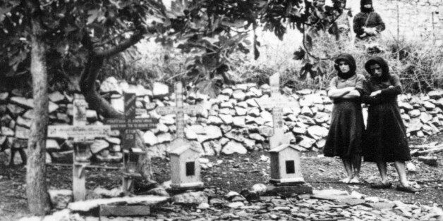 Women standing In the graveyard of Distomo, Greece, where victims of a 1944 Nazi massacre are buried,...