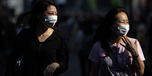 SEOUL, SOUTH KOREA - JUNE 12: People wear masks as a precaution to protect them against the MERS virus...