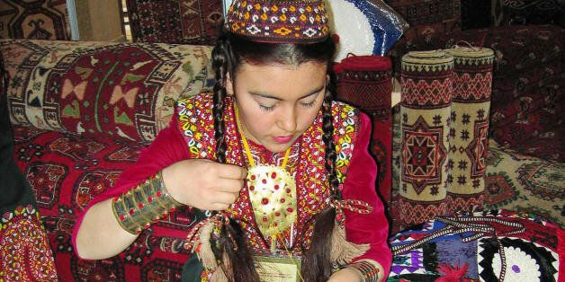 A seamstress embroiders as she sits on carpets during a Day of Turkmen carpets national holiday in Ashgabad...