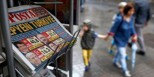 People walk past a kiosk with newspapers featuring front-page coverage of Sunday's elections, in Istanbul,...