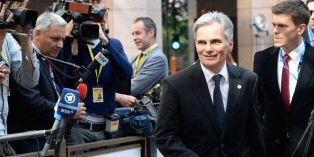 Austria's Chancellor Werner Faymann (R) arrives at the European Council headquarters for an extraordinary...