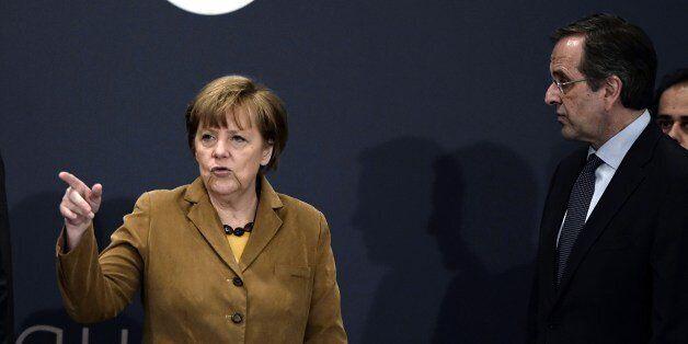 German Chancellor Angela Merkel (L) talks with Greece's Prime minister Antonis Samaras upon their arrival...