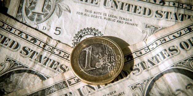 A one euro coin is pictured on one US dollar notes on March 13, 2015 in Godewaersvelde, Northern France....