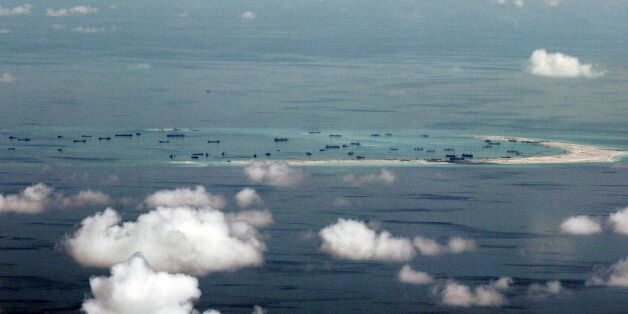 This areal photo taken through a glass window of a military plane shows China's alleged on-going reclamation...