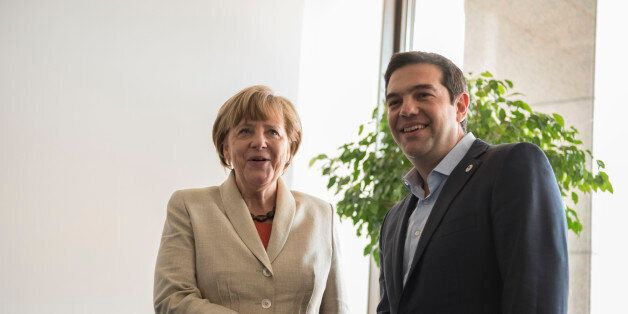 Greek Prime Minister Alexis Tsipras (R) walks with Greek Finance Minister Yianis Varoufakis at the finance...
