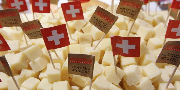 BERLIN, GERMANY - JANUARY 21: Swiss flags stick out of cubes ofAppenzeller Swiss cheese at a stand at...