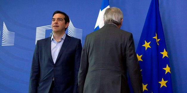 European Commission President Jean-Claude Juncker, right, stands next to Greek Prime Minister Alexis...