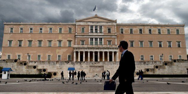 A woman walks in front of the Greek Parliament in Athens on April 7, 2015. Greek lawmakers voted on April...