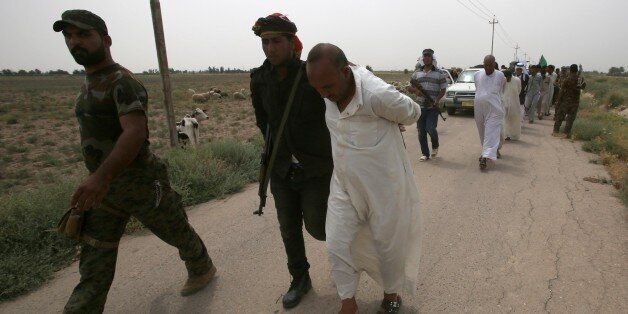 Iraqi pro-government militiamen escort men they detain for investigation after the liberation from Islamic...