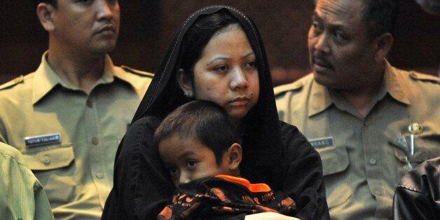Γυναίκα από την Ινδονησία η οποία η οποία καταδικάστηκε σε θάνατο στη Σαουδική Αραβία. Κρατά στα χέρια...