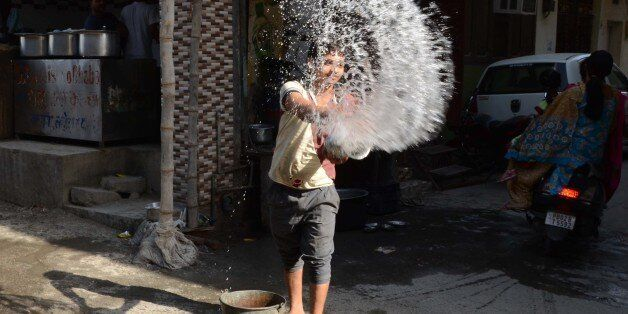 An Indian worker throws water outside a resteraunt in Amritsar on May 26, 2015, in an attempt to keep...