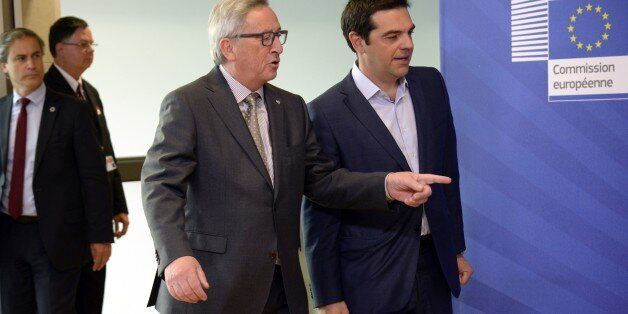 Prime Minister of Greece Alexis Tsipras (L) walks with European Union Commission President Jean-Claude...