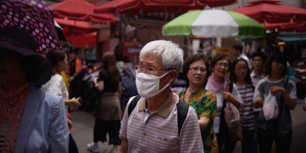 A man wearing a face mask walks through a market in Seoul on June 1, 2015. South Korean President Park...