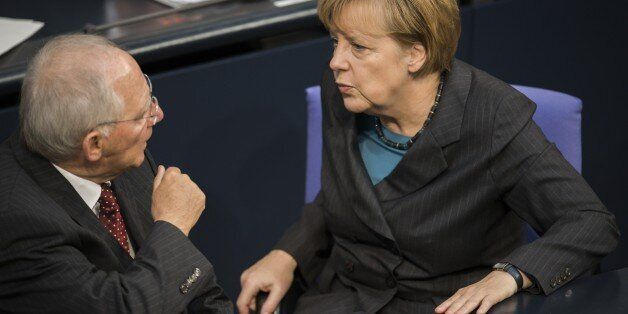 German Chancellor Angela Merkel (R) speaks with German Finance minister Wolfgang Schaeuble during a session...