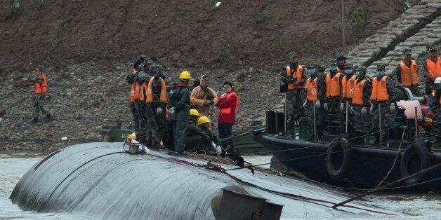 Rescue workers are seen on the hull of a capsized passenger ship Dongfangzhixing or 'Eastern Star' in...