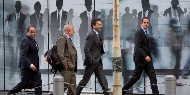 Dutch Finance Minister Jeroen Dijsselbloem, center right, walks with officials as he arrives for a meeting...