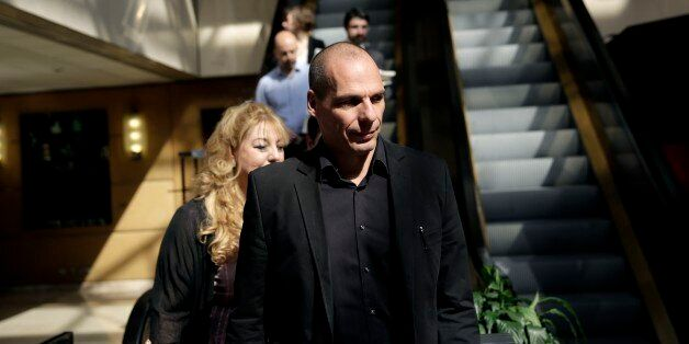 Greek Finance Minister Yanis Varoufakis, right, arrives at an economic conference in Athens, on Tuesday,...