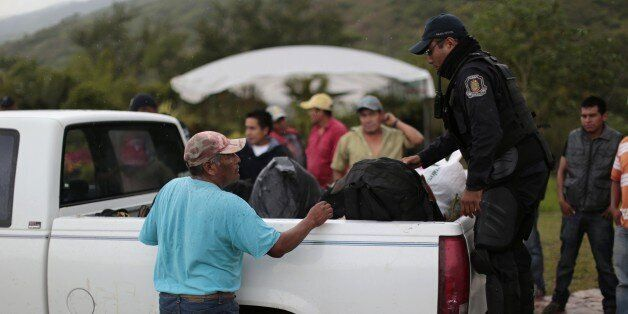 A member of the Guerrero state police (R) inspects the back of a truck at a checkpoint entering the city...