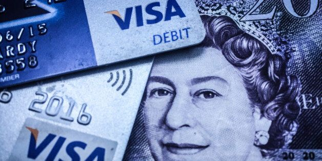 BRISTOL, ENGLAND - MAY 21: In this photo illustration a credit card is seen on top of cash on May 21,...