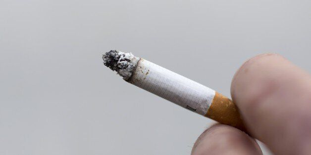 A man smokes a cigarette on May 9, 2015 in Paris. AFP PHOTO / KENZO TRIBOUILLARD (Photo credit should...