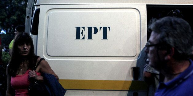 A woman stands in front of a van of the Greek state television ERT headquarters on June 16, 2013 in Athens....