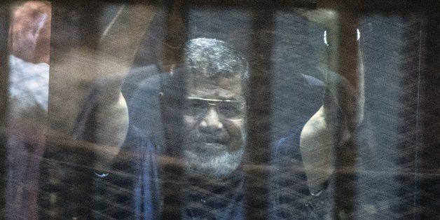 Egypt's deposed Islamist president Mohamed Morsi raises his hands from behind the defendant's cage as...