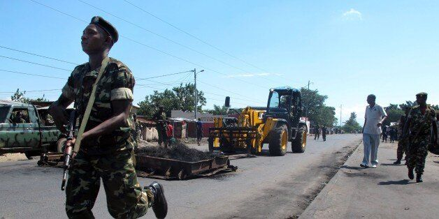 Members of the military escort a forklift as barricades erected by demonstrators are removed in the Cibitoke...