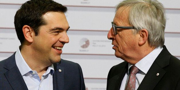 European Commission President Jean-Claude Juncker, right, speaks with Greek Prime Minister Alexis Tsipras...