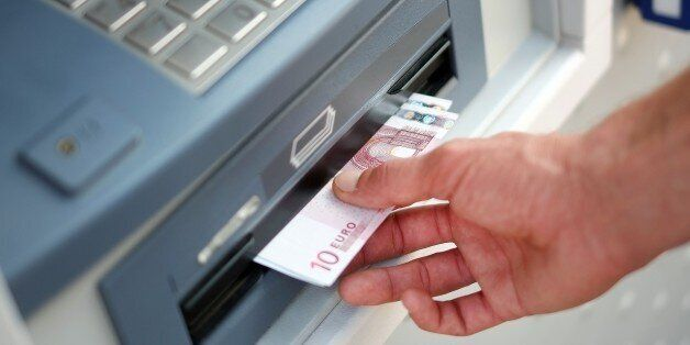 A man takes out Euro banknotes from an automated teller machine (ATM) at a cash point of the French bank...