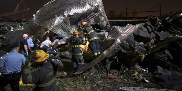 Emergency personnel work the scene of a train wreck, Tuesday, May 12, 2015, in Philadelphia. An Amtrak...