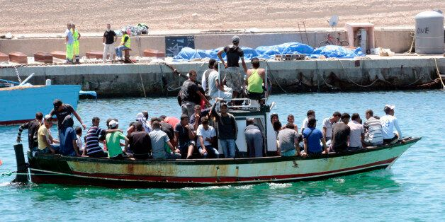 A boat filled of migrants sails past the dock on Lampedusa Italy, where are seen covered bodies and coffins...