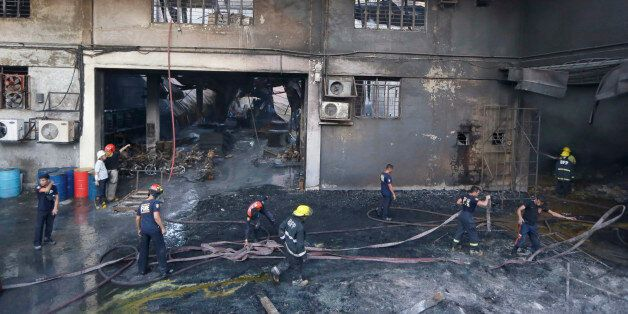 Firemen work to put the fire under control at a still-smoldering Kentex rubber slipper factory in Valenzuela...