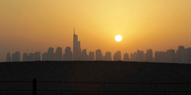 The sun sets behind the city skyline at the Marina district as the Almas tower is seen in Dubai, United...