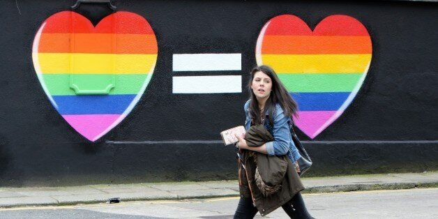 A woman walks past a mural in favour of same-sex marriages in Dublin on May 21, 2015. Ireland goes to...