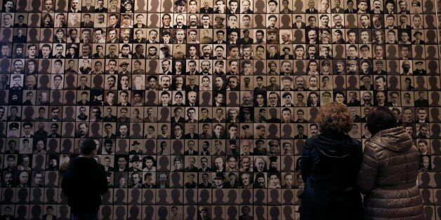 In this photo taken Saturday, March 21, 2015, visitors look at portraits of victims at the Holocaust...