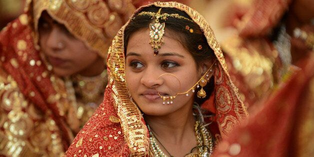 An Indian Muslim bride gestures during a mass wedding ceremony at the ancient Sarkhej Roja in Ahmedabad...