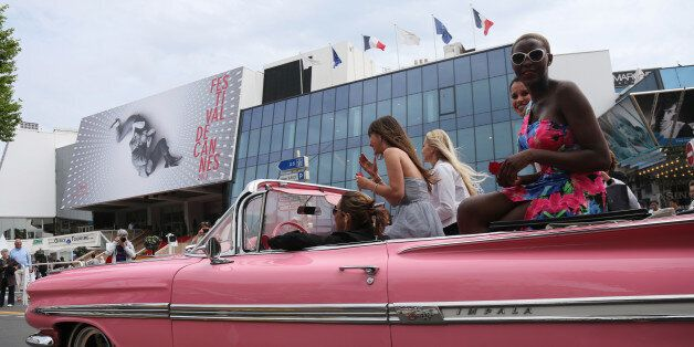 Girls drive on the Croisette in a Chevrolet Impala few hours prior the opening of the 66th edition of...