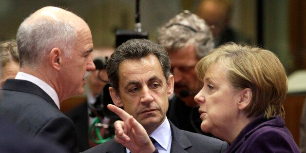 German Chancellor Angela Merkel, right, speaks with Greek Prime Minister George Papandreou, left, and...