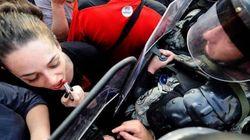 Η ιστορία πίσω από τη φωτογραφία της διαδηλώτριας με το κραγιόν απέναντι στα