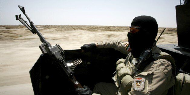 An Iraqi government forces member sits in the back of a vehicle in the Jurf al-Sakher area, some 50 kilometres...
