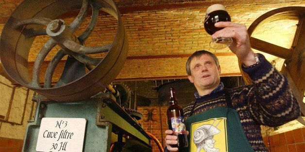 Francois Tonglet, owner of the Caracole brewery, holds up a glass of his own brew in Falmignoul, Belgium,...