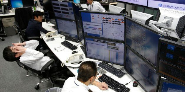 Money traders work at a computer terminal at a foreign exchange brokerage in Tokyo, Friday, Dec. 5, 2014....
