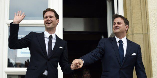 Luxembourg Prime Minister Xavier Bettel (R) holds hands with his companion Belgian architect Gauthier...