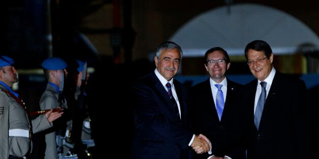Cyprus' president Nicos Anastasiades, right, and Turkish Cypriot leader Mustafa Akinci shake hands as...