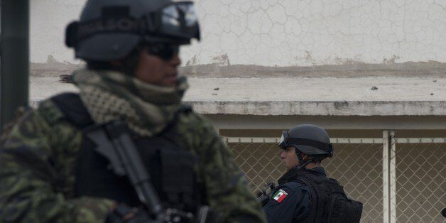 A federal policeman (R) and a soldier (L) stand guard before the presentation of Juan Manuel Rodriguez...