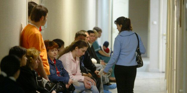 People sit in a hallway at the Saratov regional AIDS center, waiting for blood tests and other medical...