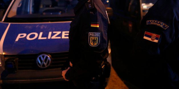 A member of the German border police, center, passes by his vehicle while monitoring a stretch of the...